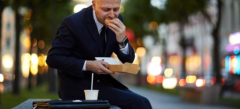 a man eating a burger on a bench seat